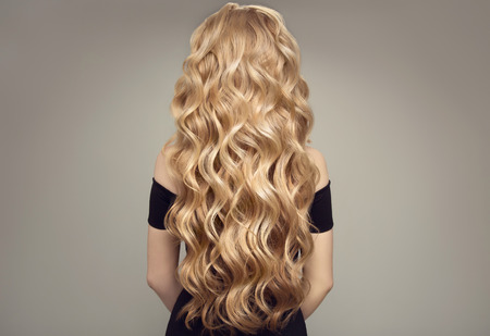 Blond woman with long curly beautiful hair. Back view. Stock Photo