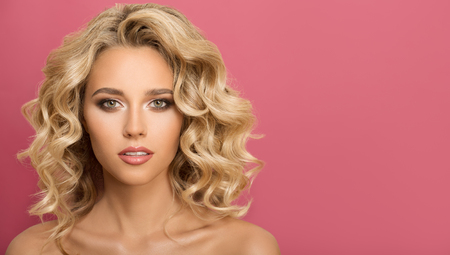 Blonde woman with curly beautiful hair on pink background. 版權商用圖片