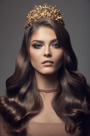 Beautiful woman in gold crown on her head. Long wavy brown hair. Stockfoto