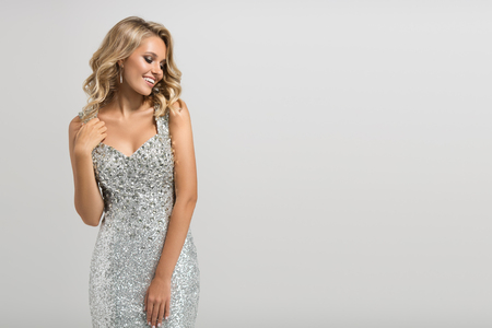 Beautiful woman in shining silver dress on gray background. Stock Photo - 88777017