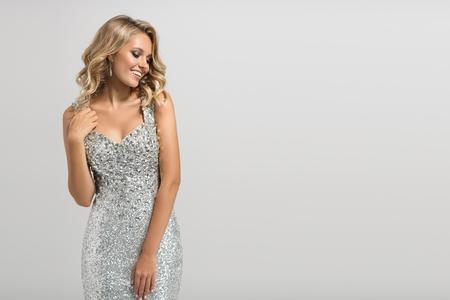 Hermosa mujer en brillante vestido de plata sobre fondo gris. Foto de archivo
