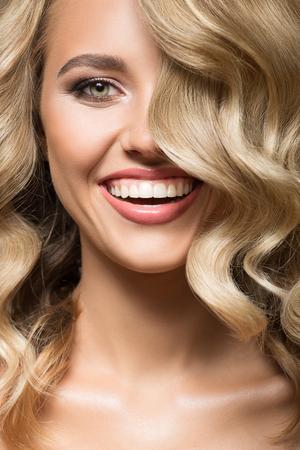 Blondevrouw met het krullende mooie haar glimlachen. Portret dichten. Stockfoto