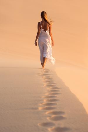 Woman in white dress walking on desert sand