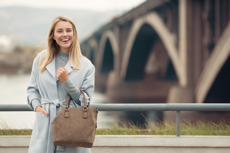 Young woman in blue coat. Autumn city background.