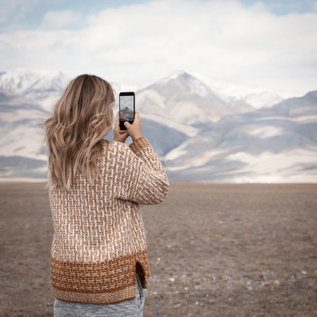 Woman traveling and taking photo. Mountains at background.