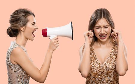 Conflicto. Una mujer le grita por un megáfono a otra mujer. Fondo rosa.