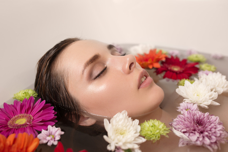 Young woman relaxing in bath with flowers.