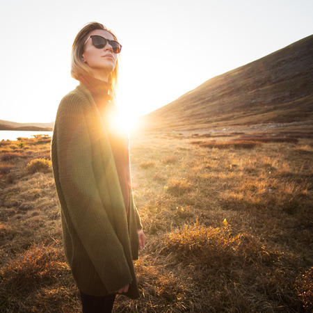Hipster girl in sunglasses outdoor. Sunset at background.