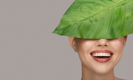 Woman smile and green leaf. Organic beauty. Gray background. Foto de archivo