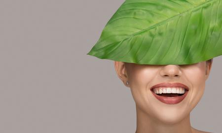 Woman smile and green leaf. Organic beauty. Gray background. 版權商用圖片