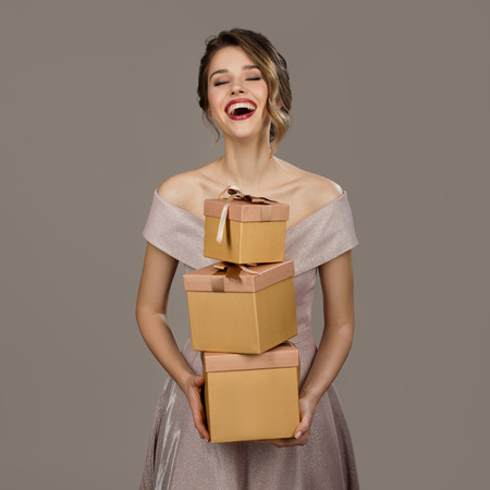Portrait of smiling pretty woman holding a gift boxes in hands. Gray background.