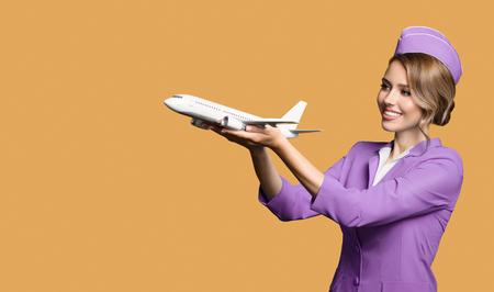 Cheerful stewardess holding airplane in hand.