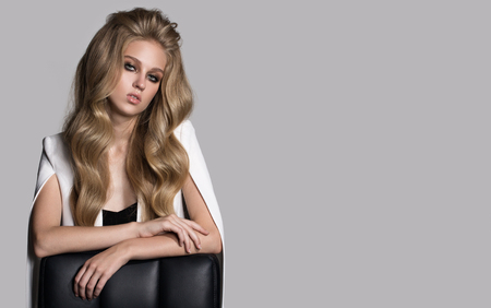 Portrait of fashion woman with long wavy blonde hair. Gray background.