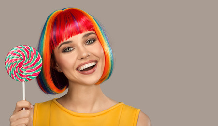 Cheerful smiling woman with bright colorful hair holding big lollipop.
