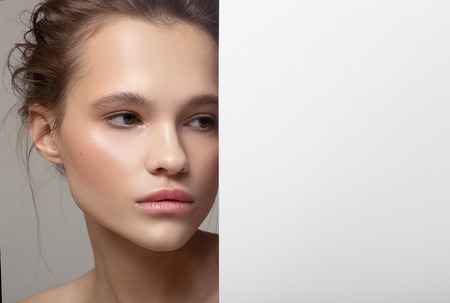 Close up fashion portrait of beautiful woman. Clear natural skin. White paper blank. 版權商用圖片