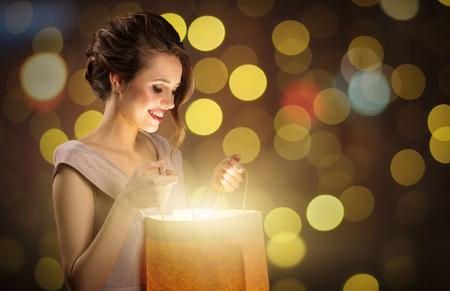 Attractive surprised woman holding magic shopping bag. Bokeh lights at background. 版權商用圖片