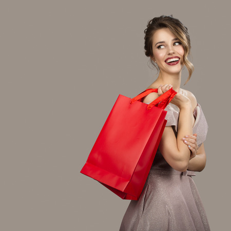 Cheerful woman in evening dress holding red shopping bags. Gray background.