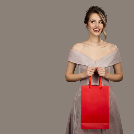 Cheerful woman in evening dress holding red shopping bag. Gray background. 版權商用圖片