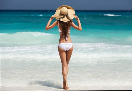 Schöne schlanke Frau im weißen Bikini und Hut. Genießen Sie tropisches Sonnenbaden. Standard-Bild