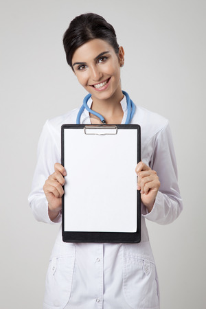 Happy doctor holding empty blank in hands 版權商用圖片