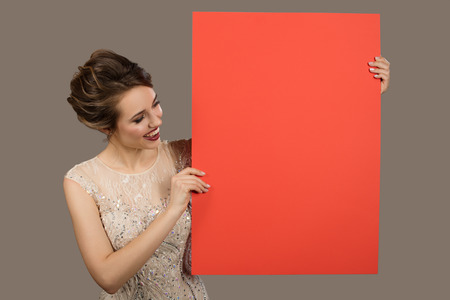 Charming happy woman holding big red paper empty blank. Gray background.