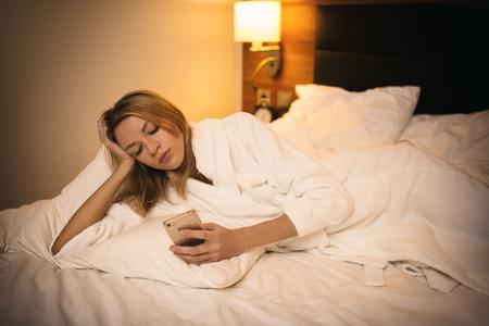Young woman using smartphone. Lying on bed in bedroom. 版權商用圖片