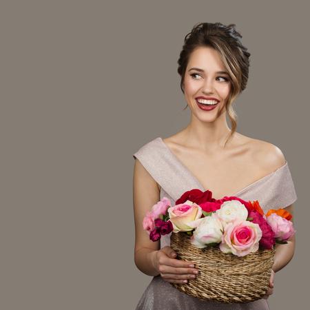 Portrait of pretty smiling woman holding flowers. Gray background. 版權商用圖片