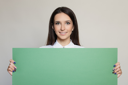 Happy attractive woman holding green empty blank.