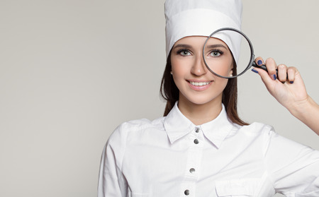 Young attractive woman doctor oculist. Gray background.