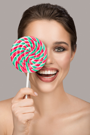 Cheerful smiling woman with big colorful lollipop. Gray background. 版權商用圖片
