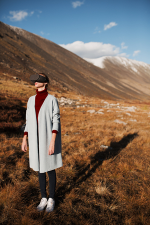 Woman in virtual reality. Mountain landscape at background.