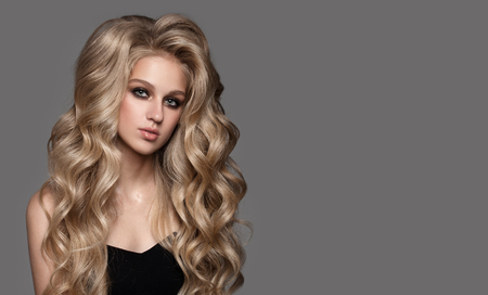 Portrait of cute woman with long wavy hair. Healthy blonde.