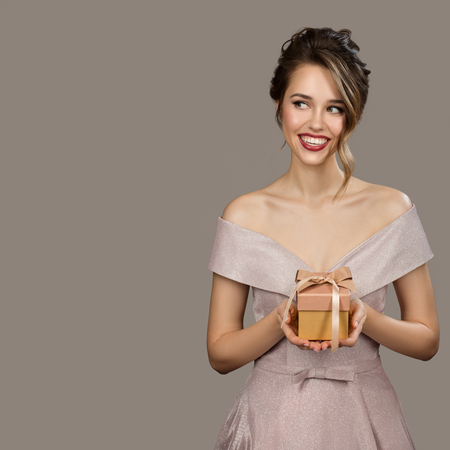 Portrait of smiling pretty woman holding a gift box in hands. Gray background.