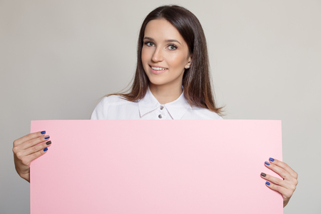 Happy attractive woman holding pink empty blank.