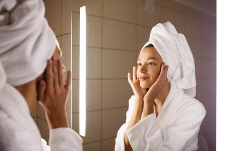 Woman looking on her mirror in bathroom 版權商用圖片