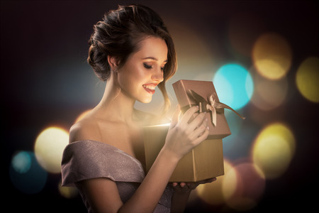 Attractive surprised woman holding magic gift box in hands. Bokeh lights at background.