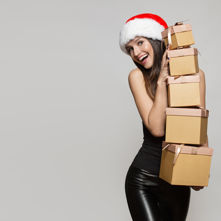 Happy woman in santa hat holding many gifts boxes. Gray background.