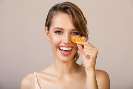 Happy woman using eye applicator mask.