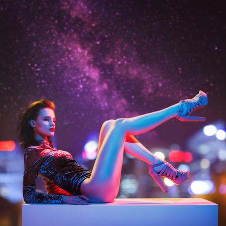 Schöne Mode-Modell-Aufstellung. Nachtstadt im Hintergrund.