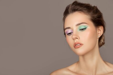 Fashion portrait of young woman. Colorful eye shadows. Perfect skin.