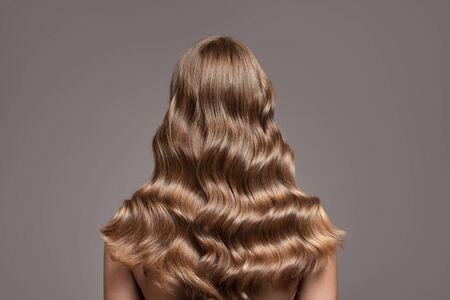 Perfect long wavy blonde hair. View from behind. 版權商用圖片 - 130778859