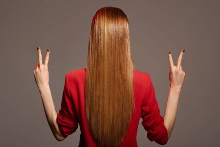 Rückansicht der schönen Frau mit roten langen Haaren.