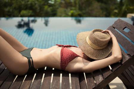 Slender girl sunbathes on a deck chair near the pool