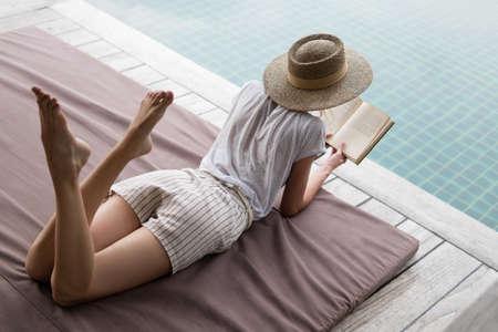 Slender girl sunbathes near the swimming pool