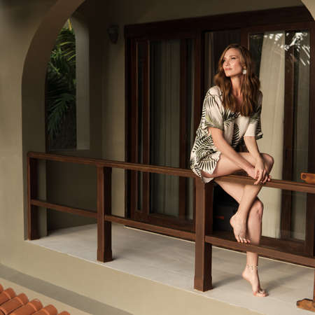 Fashionable portrait of a beautiful woman in a tropical villa