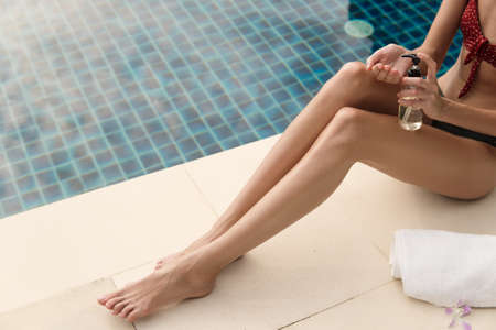 Beautiful female tanned legs on a tropical resort near swimming pool.