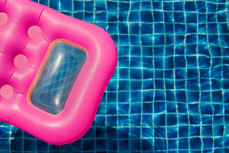 Inflatable swimming pink mattress and blue pool. Top view.