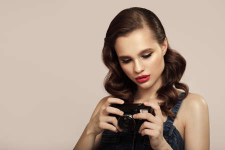 Girl in pin-up style holds a retro camera in her hand.