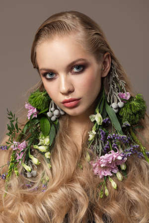 Portrait of a beautiful blonde girl with flowers in her hair Stock Photo