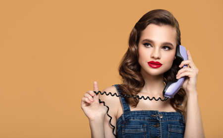 Pin-up girl holding a retro-style telephone receiver on orange background. Stock Photo